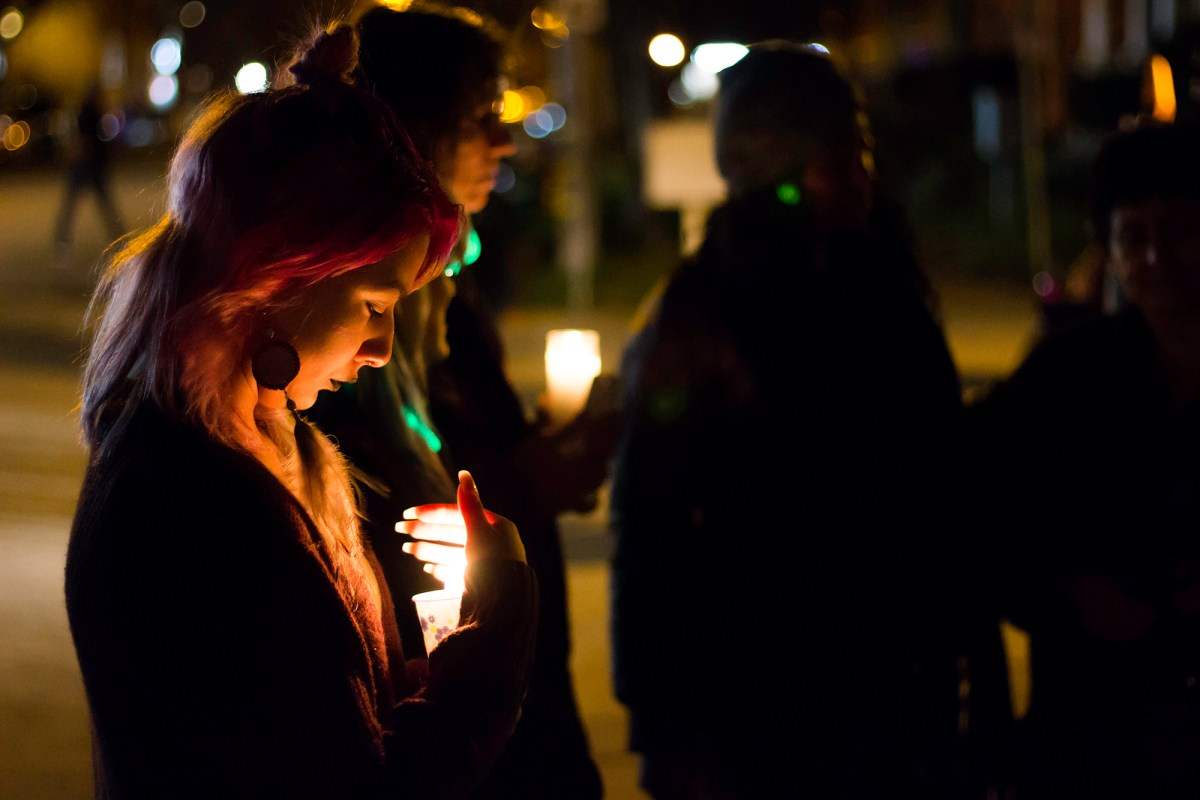 a woman with pink hair holds a candle at a vigil