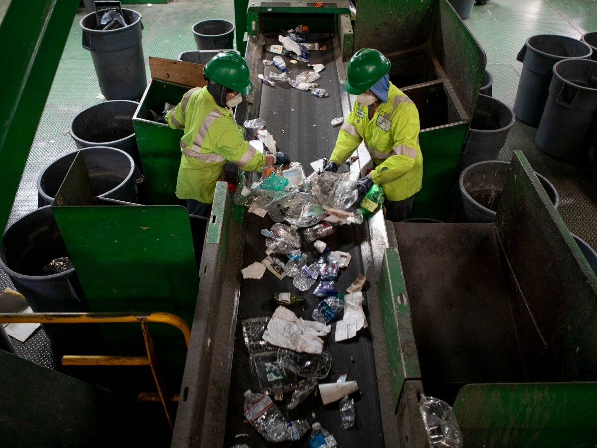 Workers sort through plastic items on a conveyor belt at greenwaste recycling facility in San Jose