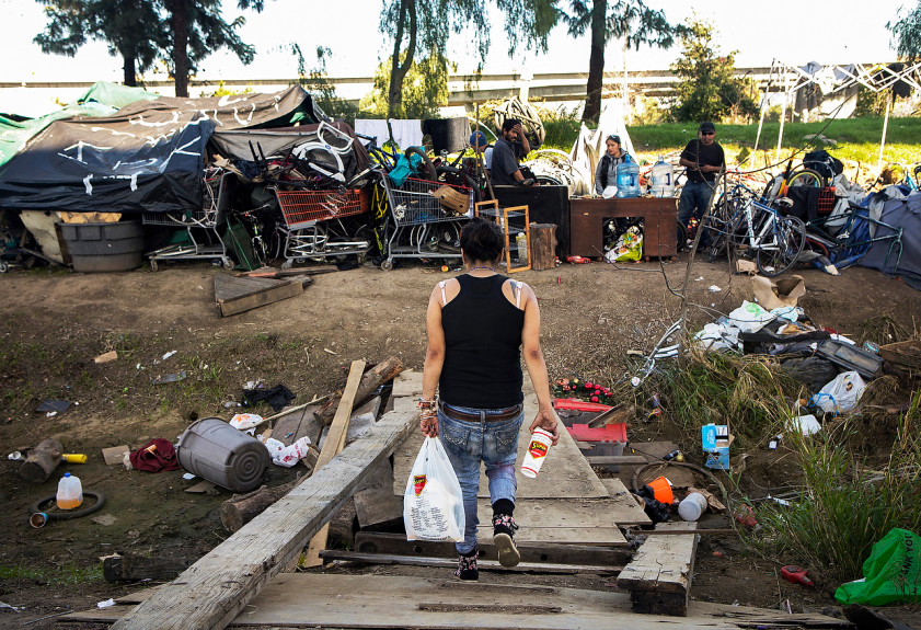 A woman walks toward friends at a homeless encampment where she lives next to the Interstates 101 and 280 in San Jose
