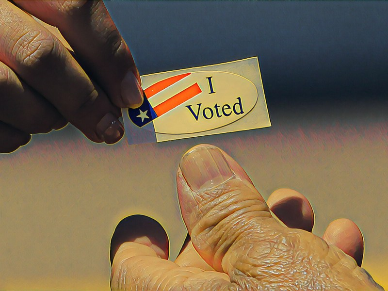"An election worker hands out an ""I voted"" sticker"