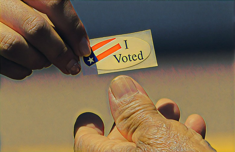"""An election worker hands out an """"I voted"""" sticker"""