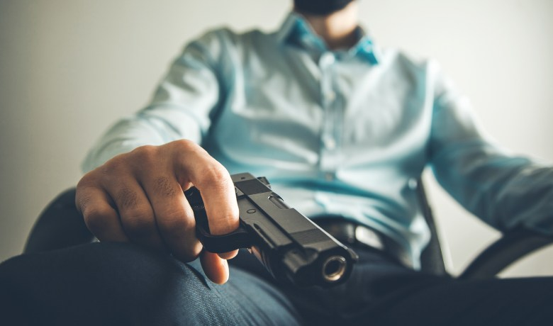 photo of sitting man hand gun in home