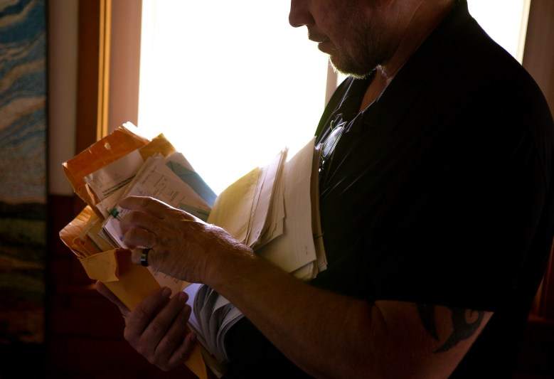 Foster parent Andrew Simmons goes through paperwork of his six adopted children in his Ramona, CA home