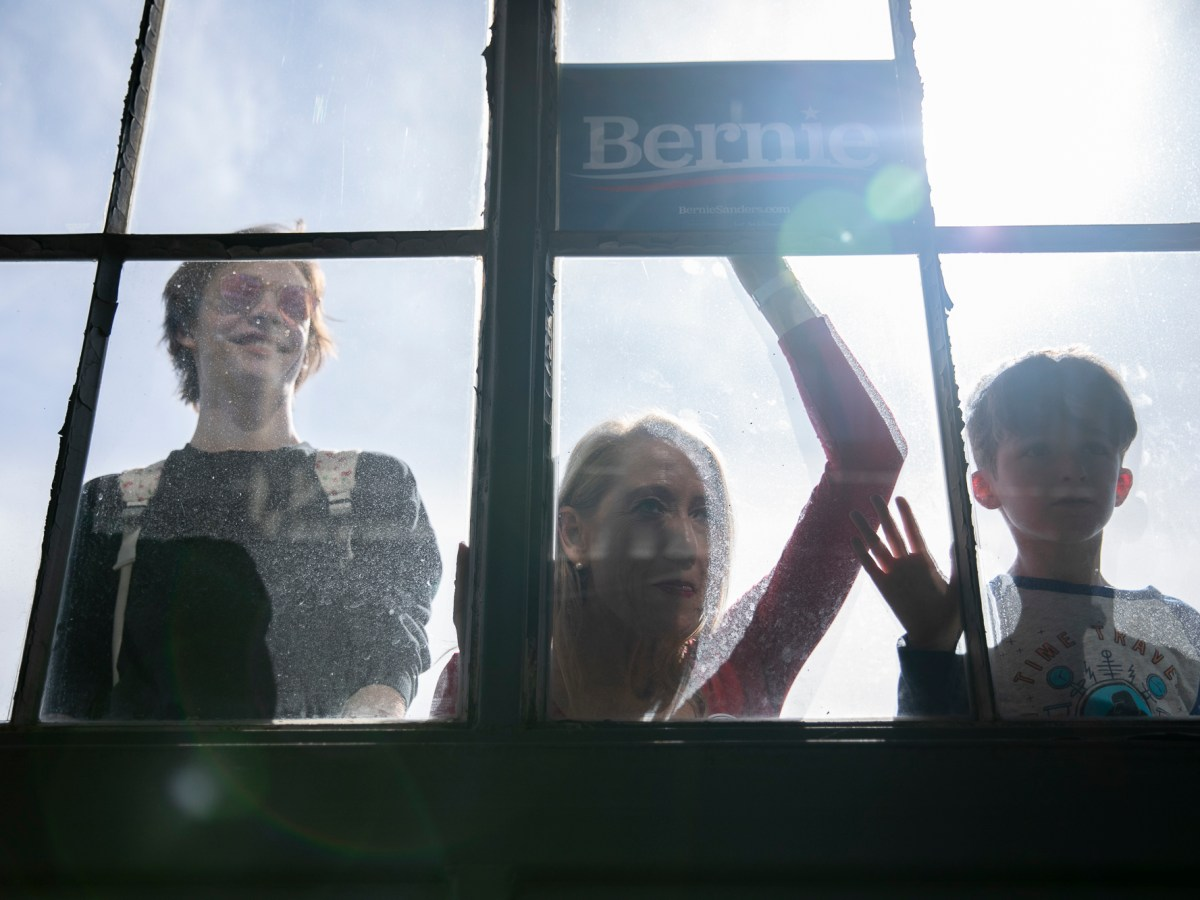 Supporters peer through the window during a Bernie Sanders presidential campaign event at Craneway Pavilion in Richmond, CA on February 17, 2020. Photo by Anne Wernikoff for CalMatters