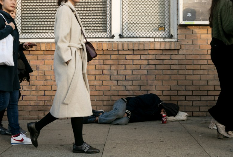 A man sleeps on Valencia street in the mission district of San Francisco. Photo by Anne Wernikoff for CalMatters