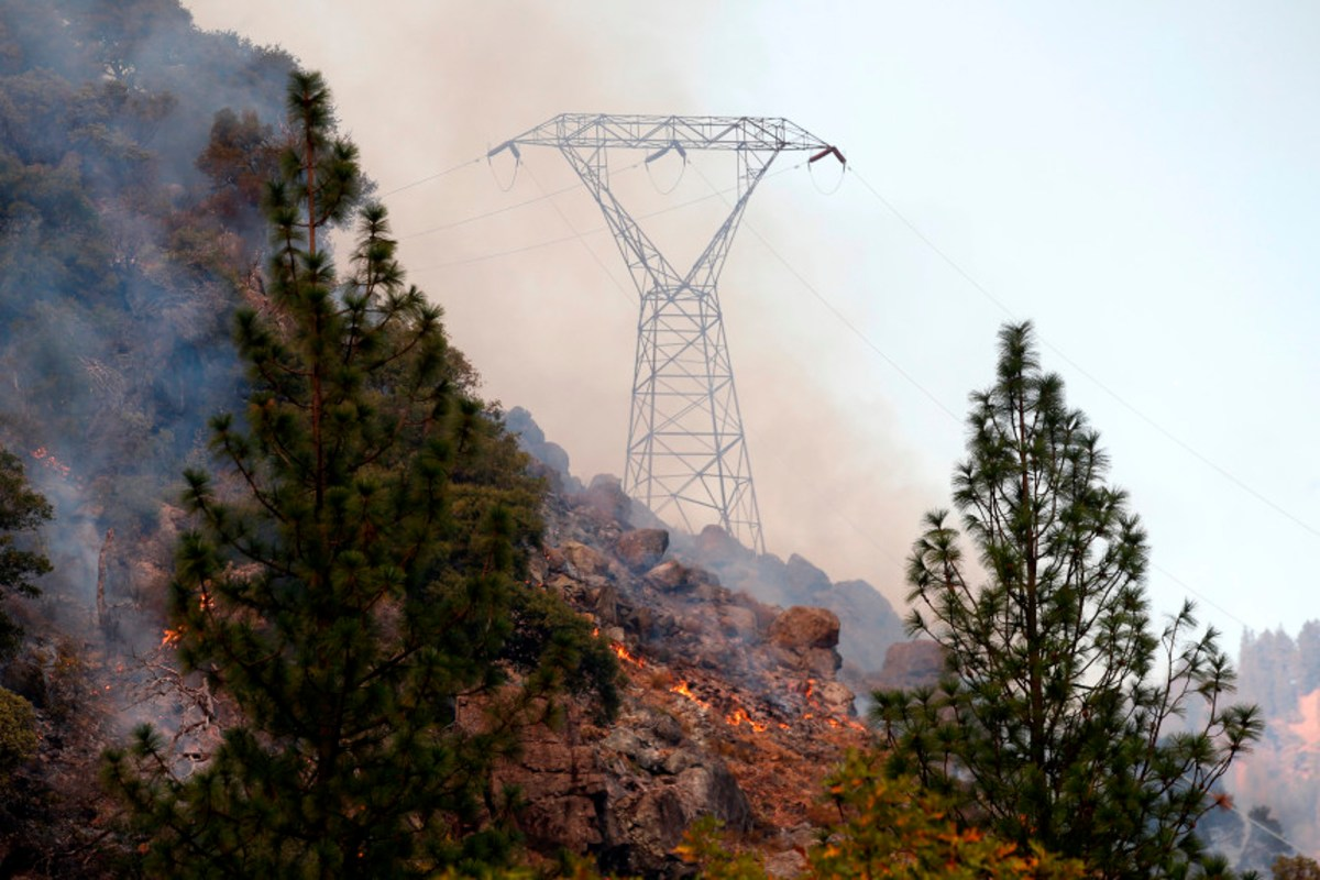Fire smolders under high voltage towers in Pulga, Calif., November 9, 2018