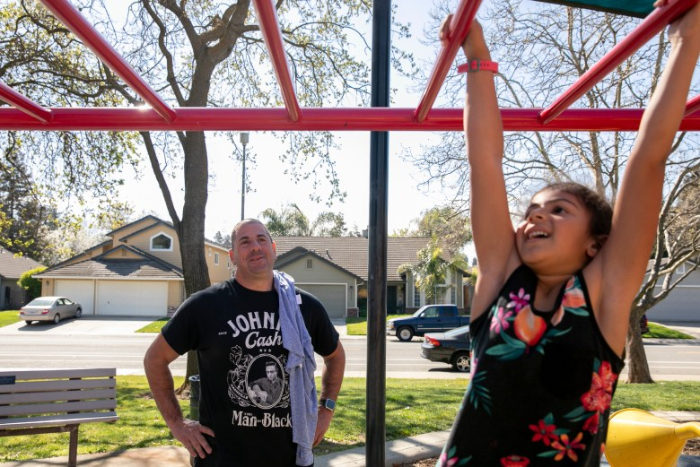 Stuart Levin watches his daughter Arabella, 6, swing from the monkey bars at Kloss park. Levin is enjoying the additional time with this children while they are out of school. Elk Grove Unified closed all district schools until March 13 after a student tested positive for COVID-19. Photo by Anne Wernikoff for CalMatters