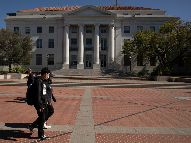 Students wearing surgical masks walk through Sproul Plaza, normally bustling with student organization tables, on March 12, 2020. UC Berkeley suspended most in-person classes in March due to Coronavirus concerns. Photo by Anne Wernikoff for CalMatters