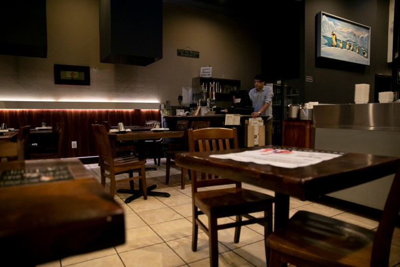 Bowl'd General Manager Ruben Hernandez is processing take-away orders in the empty dining room of the Korean BBQ restaurant Oakland on March 16, 2020 for the novel coronavirus.  Photo by Anne Wernikoff for CalMatters