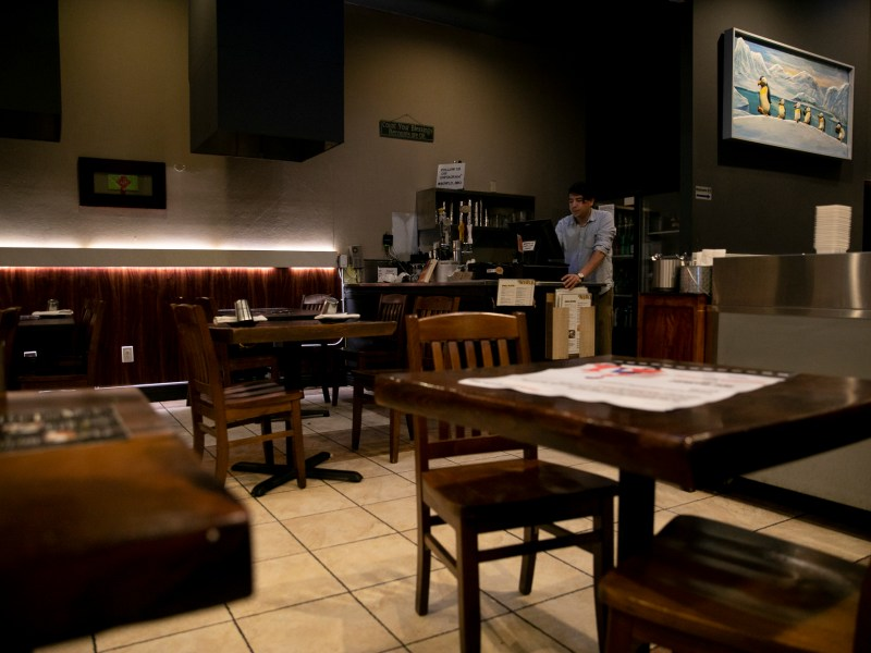 Bowl'd general manager Ruben Hernandez processes take-out orders in the Oakland Korean BBQ restaurant's empty dining room on March 16, 2020. Today Alameda and surrounding counties announced an order to shelter in place until April 7 in an effort to curb the spread of the novel coronavirus. Photo by Anne Wernikoff for CalMatters