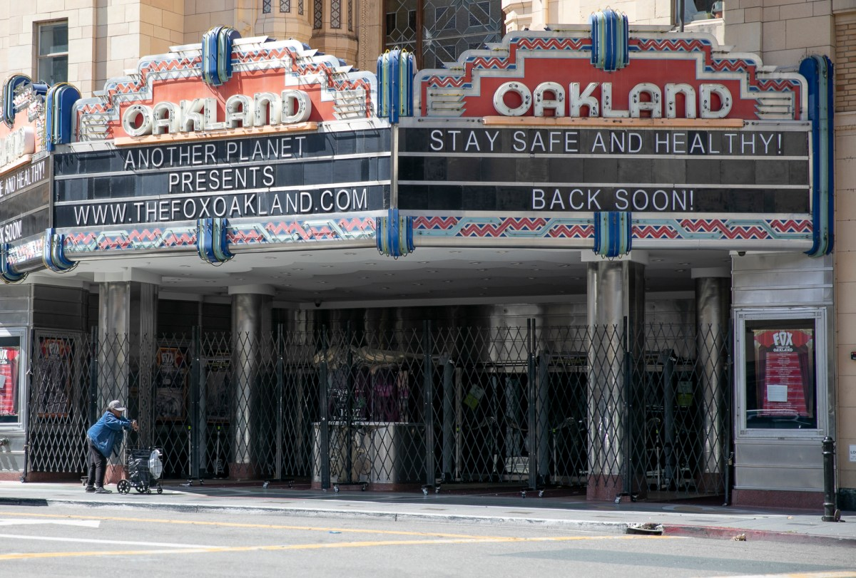 A woman pushes a cart past the shuttered Fox Theater in downtown Oakland on March 25, 2020. Today it was announced that Alameda, along with five area counties, would extend school closures through May 1 in an effort to limit the spread of COVID-19. Photo by Anne Wernikoff for CalMatters