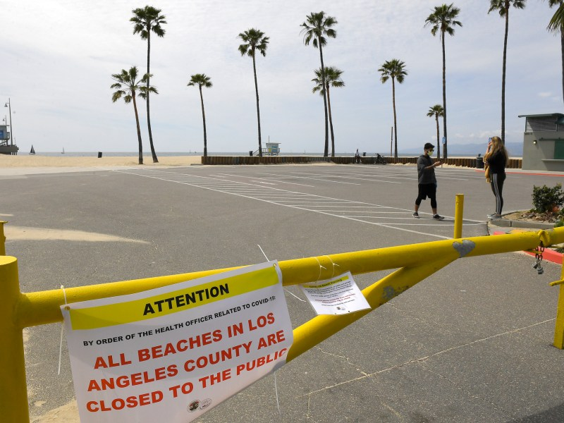 "Pedestrians walk through an empty parking lot at Venice Beach on March 28 — a week after Gov. Gavin Newsom barred 40 million residents from going outdoors except for essentials. Some evidence suggests that may be helping California ""bend the curve"" of rising coronavirus casualties. Photo by Mark J. Terrill, AP Photo"