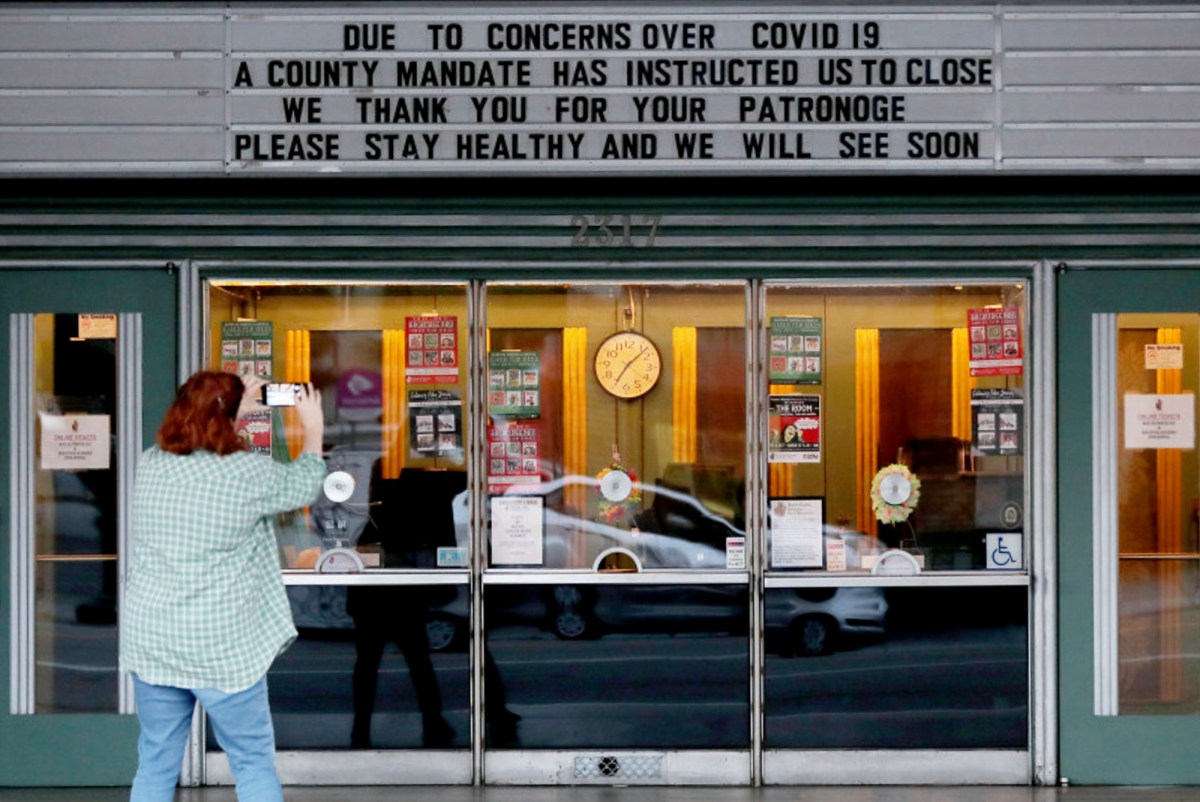 A woman takes photos of the Alameda Theater marquee in Alameda, Calif., on Tuesday, March 17, 2020. Seven Bay Area counties ordered shelter-in-place to reduce the spread of COVID-19. Photo by Ray Chavez, Bay Area News Group