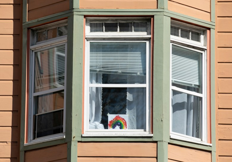 A rainbow taped to a window in the Richmond district of San Francisco on April 7, 2020. People across the globe have been posting rainbows in their windows as a sign of solidarity and hope during social distancing. Photo by Anne Wernikoff for CalMatters