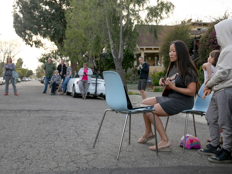 Patti Wang-Cross plays the ukulele as neighbors sing 'You Are My Sunshine,' 'Happy Birthday,' and songs by Bruno Mars during their weekly sing-along. The neighbors began the Wednesday night tradition in response to social distancing rules in light of concerns over the coronavirus in California. Photo by Anne Wernikoff for CalMatters
