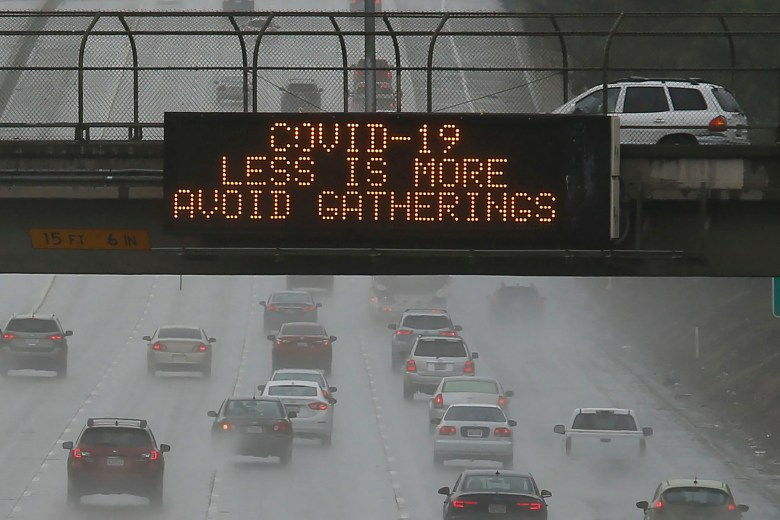 Vehicles pass a COVID-19 warning sign on westbound Highway 50 in Sacramento, Calif., Saturday, March 14, 2020.