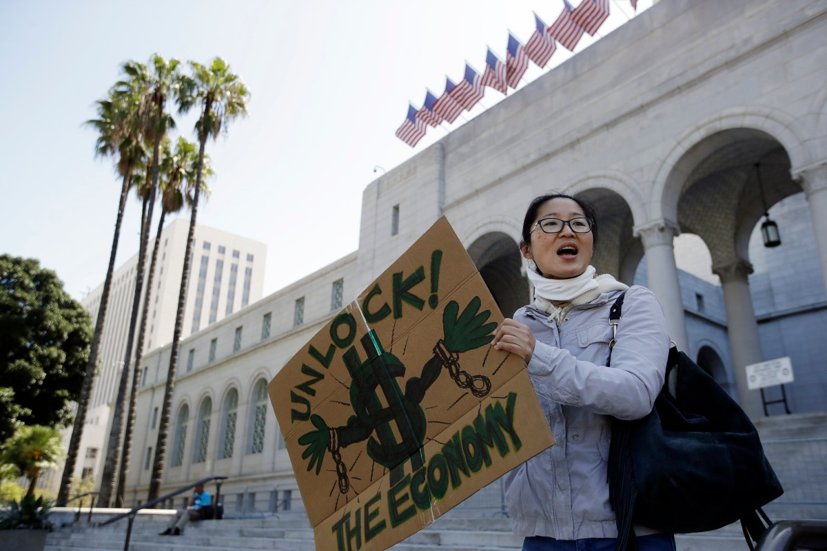 A protester shouts slogans during a rally calling for an end to California Gov. Gavin Newsom's stay-at-home orders, a response to the COVID-19 pandemic, outside of City Hall in downtown Los Angeles, April 22, 2020. Photo by Marcio Jose Sanchez, AP Photo
