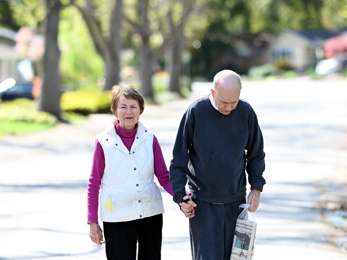 Sue Swezey, 83, stands with her autistic son John Swezey, 57, in Menlo Park, California on March 30, 2020