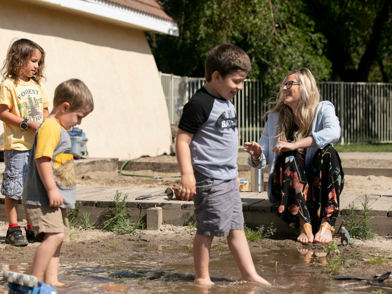 Amanda Simoni, owner of Heritage School of Discovery in Oakdale, laughs while students play in the school yard mud pit. A new California child care website aims to connect essential workers with available options. Photo by Anne Wernikoff for CalMatters