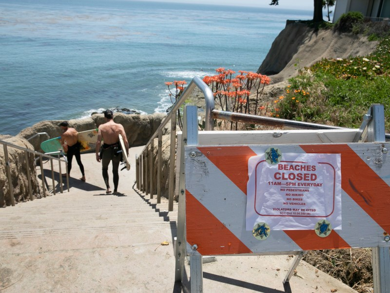 Surfers carry their boards down to the water at noon despite daytime beach closures at Pleasure Point in Santa Cruz on May 7, 2020. Photo by Anne Wernikoff for CalMatters
