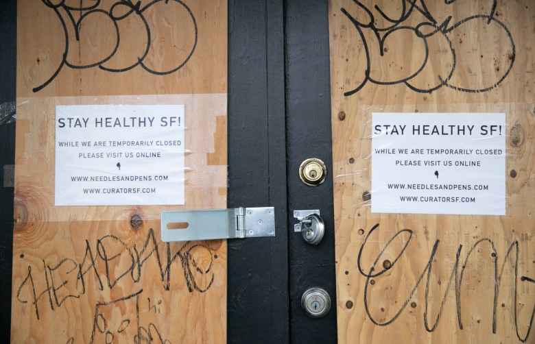 A boarded up door with an open padlock in the Mission neighborhood of San Francisco on May 18, 2020. Today, retail stores in San Francisco, Marin and San Mateo counties were permitted to re-open for curbside pick-up. Photo by Anne Wernikoff for CalMatters