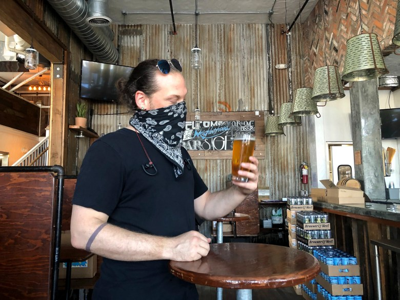 Dylan Powers, 40, assistant brewer, samples a new habanero Pilsner in the bar of Sage Plant Based Bistro. Photo by Nigel Duara for CalMatters