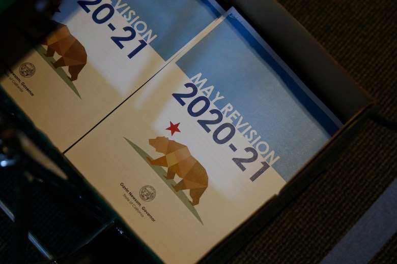 Copies of Gov. Gavin Newsom's revised 2020-2021 state budget are seen at a news conference in Sacramento on May 14, 2020. Photo by Rich Pedroncelli, AP Photo/Pool