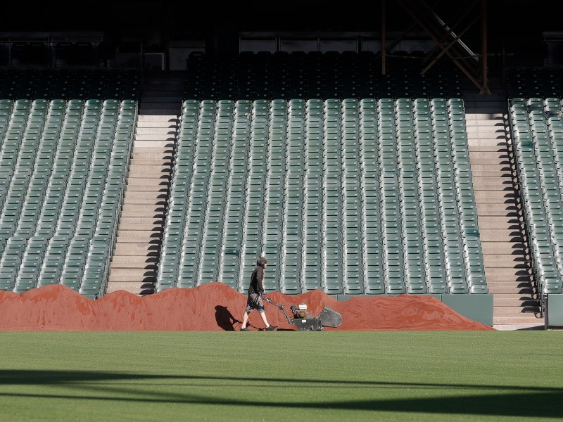 A grounds crew worker pushes equipment at Oracle Park, the San Francisco Giants' baseball ballpark, in San Francisco on March 26, 2020. The opening of baseball season was delayed due to the novel coronavirus pandemic. Photo by Jeff Chiu, AP Photo