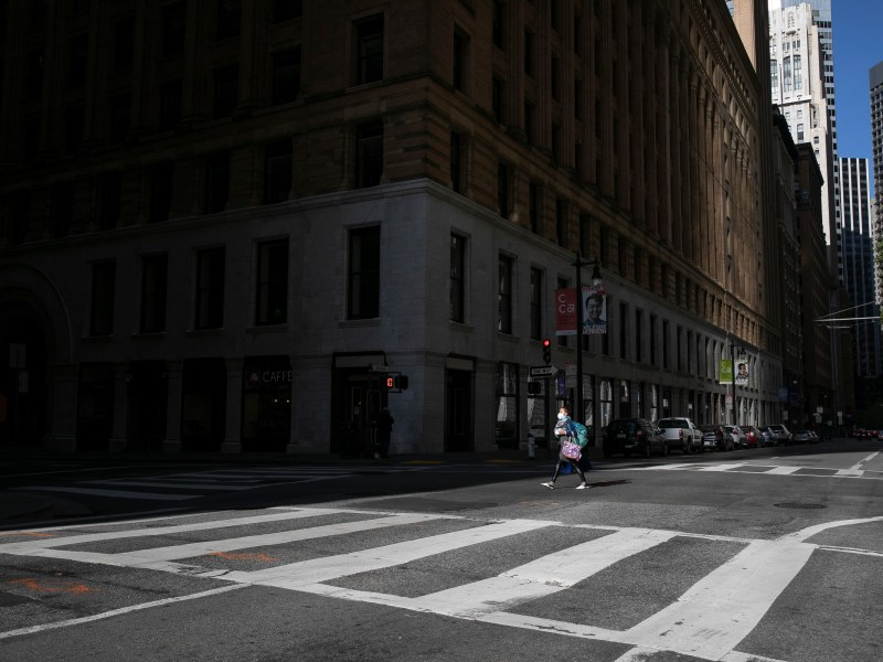 A pedestrian crosses an empty intersection in San Francisco financial district at evening rush hour on May 7, 2020. Photo by Anne Wernikoff for CalMatters