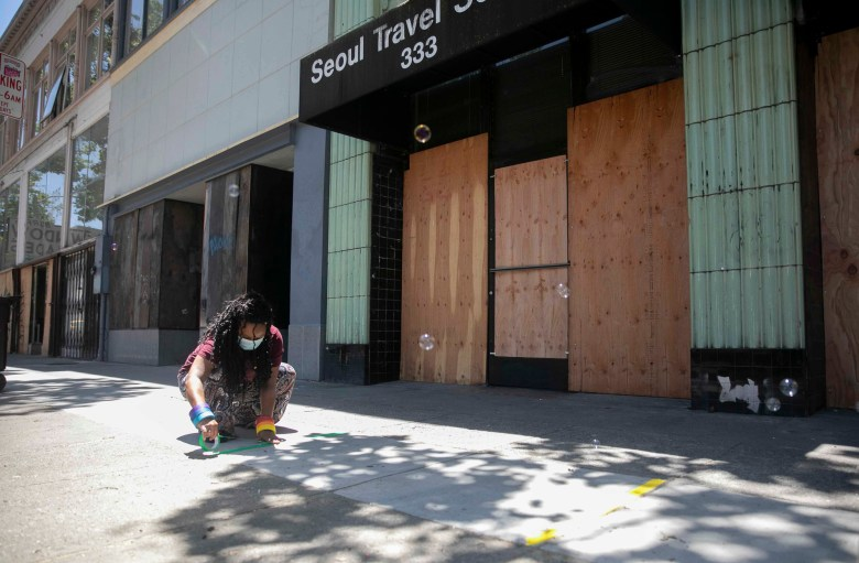 Store manager Geneva Demmitt prepares for a crowd of customers by placing rainbow strips of tape six feet apart on the sidewalk in front of boarded up businesses along 14th street in downtown Oakland. All of the businesses on this were vandalized during recent protests earlier this week against police violence. Photo by Anne Wernikoff for CalMatters