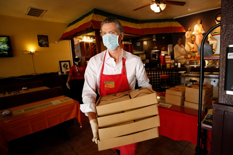 Gov. Gavin Newsom carries meals made at the Queen Sheba Ethiopian Cuisine restaurant to a waiting delivery vehicle in Sacramento on June 19, 2020. Newsom visited the restaurant that is participating in the Great Plates Delivered program that provides meals to older adults who are at-risk to COVID-19. Photo by Rich Pedroncelli, AP Photo/Pool
