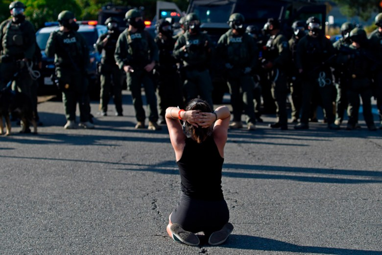 A protester kneels in front of police after blocking the I-680 north bound freeway during a Black Lives Matter protest in Walnut Cree on June 1, 2020. Walnut Creek Police issued a curfew tonight after looters descending into downtown and looted local businesses yesterday. Over 100 police officers from agencies around the county are in Walnut Creek patrolling the area. Photo by Jose Carlos Fajardo, Bay Area News Group