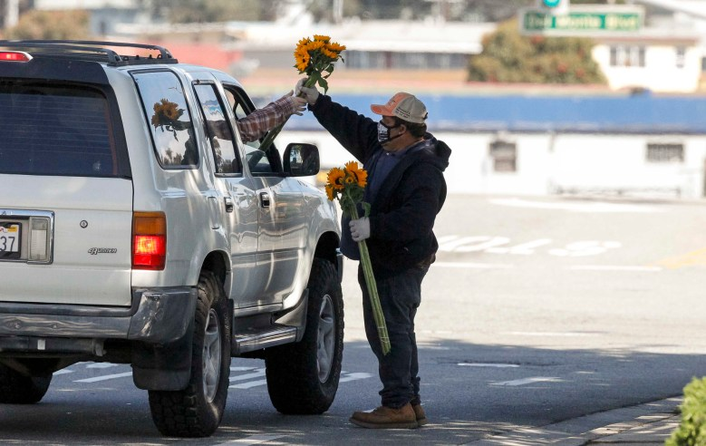 Isidoro Flores Contreras hands a customer a bouquet of sunflowers on May 15, 2020. He credits Herbalife with helping him walk again, and he believes it will also keep him safe from the novel coronavirus. Photo by Vernon McKnight / The Salinas Californian