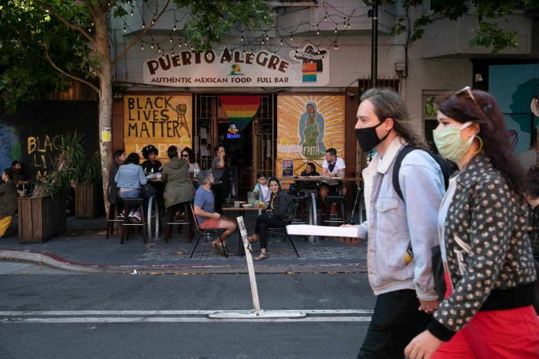 Pedestrians walk past an outdoor seating area t Puerto Alegre in the San Francisco Mission neighborhood on July 25, 2020. Several blocks of Valencia street will be shutting down to traffic on weekends to allow shops and restaurants to expand into the the street. Photo by Anne Wernikoff for CalMatters