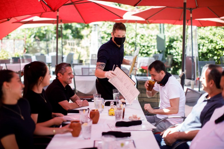 Cleverson Davis, a waiter at Palermo Italian Restaurant in San Jose tends to customers while wearing a mask on June 5, 2020. Photo by Dai Sugano, Bay Area News Group