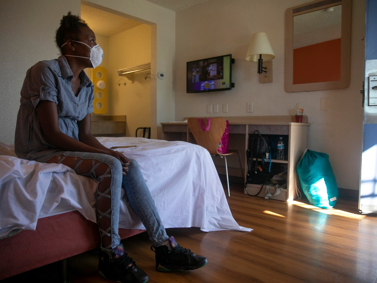 Jamie Burson sits on the bed of her motel room in Farfield on August 4, 2020. Burson, who has been living between her car and motels since being evicted in April, says she feels unsafe at the motel and plans to move again later later today. Photo by Anne Wernikoff for CalMatters