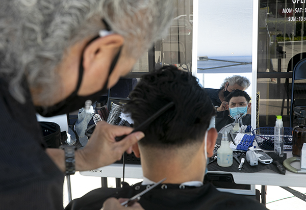 "Luis Hoang, owner of Luis Hair Salon, gives Christopher Jimenez a trim in San Jose on Aug. 14, 2020. Hoang, who was able to reopen his salon outdoors, says the arrangement is ""uncomfortable"" but he has no other choice. Photo by Anne Wernikoff for CalMatters"