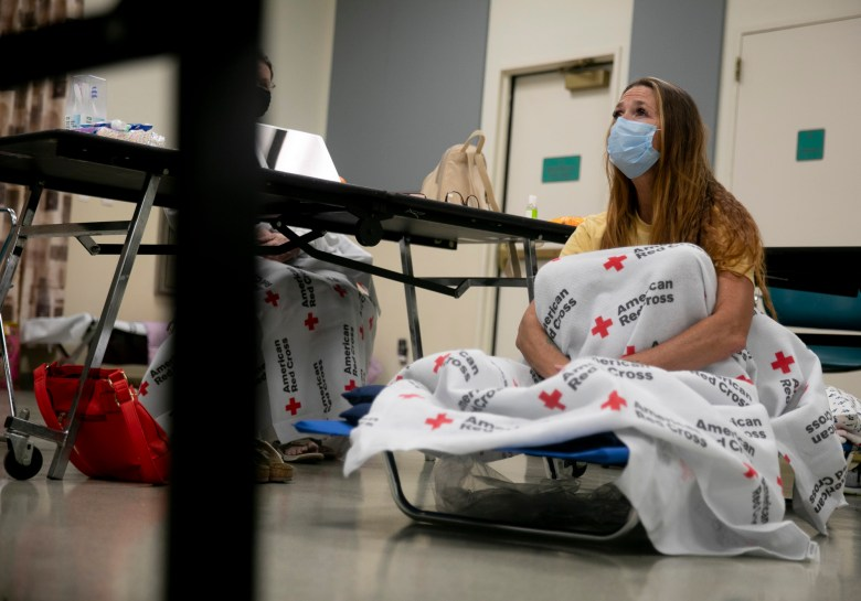 Shawnee Whaley, 57, wears a mask as she rests on a cot at the Ulatis Community Center in Vacaville after evacuating her home on August 18, 2020. Whaley said she and her mother, who lives across the street, had to leave in a matter of minutes, leaving almost everything behind. Photo by Anne Wernikoff for CalMatters
