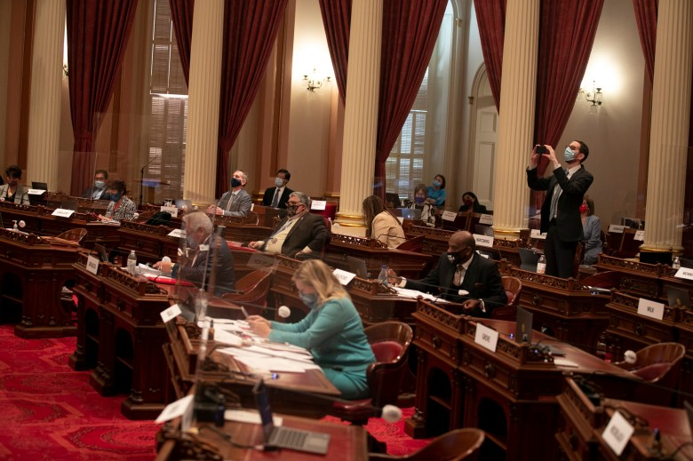Sen. Scott Wiener takes a photo of the vote tally as the eviction bill passes in the senate. Photo by Anne Wernikoff for CalMatters