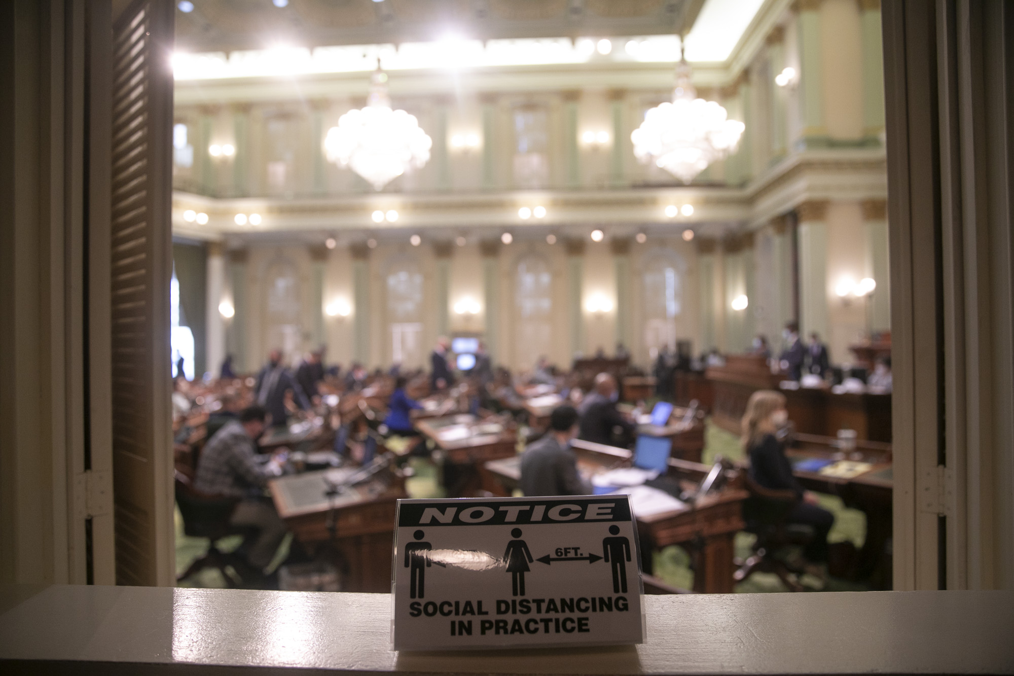 A reminder to maintain social distance is placed on the window of the press bay looking into the assembly floor on Aug. 31, 2020. Photo by Anne Wernikoff for CalMatters