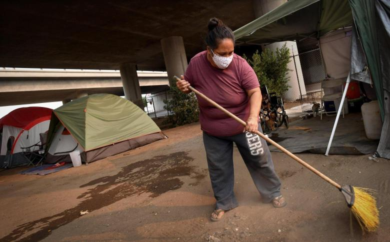 Rose Juarez DeLeon tidies up around her home, a tent under Highway 41, in a homeless encampment named the Dream Camp by residents, Thursday, Aug. 20, 2020. Fresno homeless advocate Dez Martinez set up the camp with community donations and help. She was frustrated by the lack of safety on Santa Clara Street, where hundreds of homeless individuals have set up camp, where the city has not picked up trash for months, and crime is growing. Photo by John Walker, The Fresno Bee