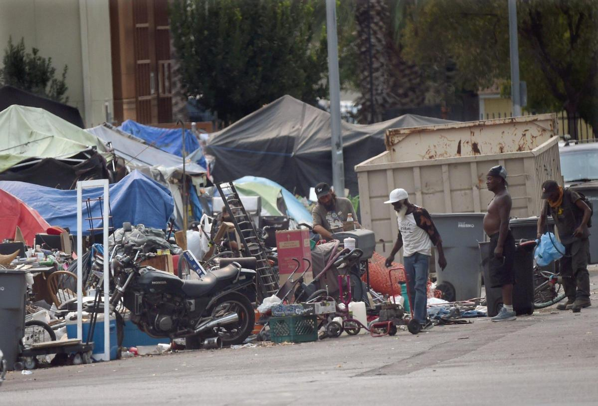 Homeless men hunt for salvageable items in piles along F Street, near Santa Clara Street and the Poverello House, Thursday, Aug. 20, 2020. Frustrated by the lack of safety on Santa Clara Street and the county's inability to shelter more people, homeless advocate Dez Martinez started a safe homeless camp on her own.