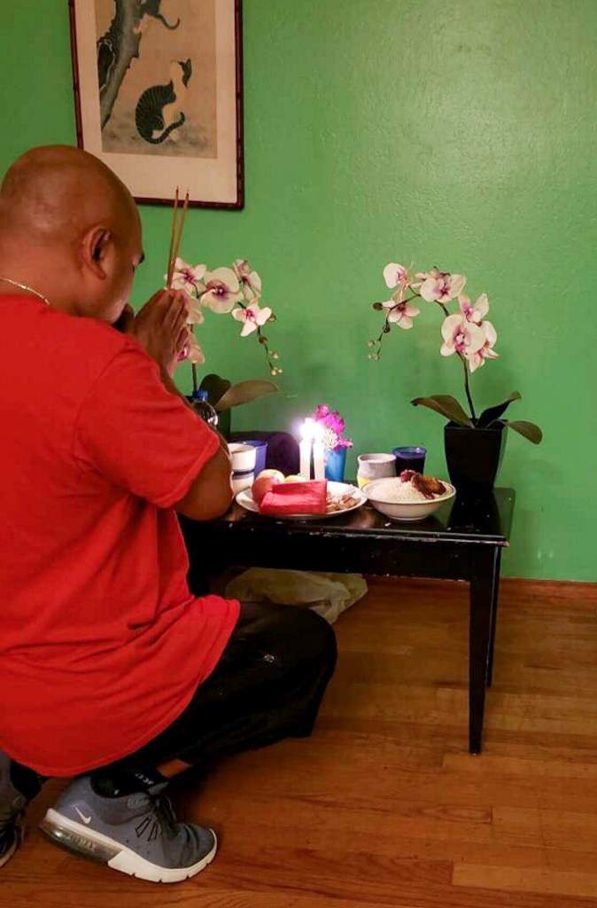Chanthon Bun, who was released from San Quentin in July, prays at a small shrine he made to honor two friends who died of COVID-19. Photo courtesy of Chanthon Bun