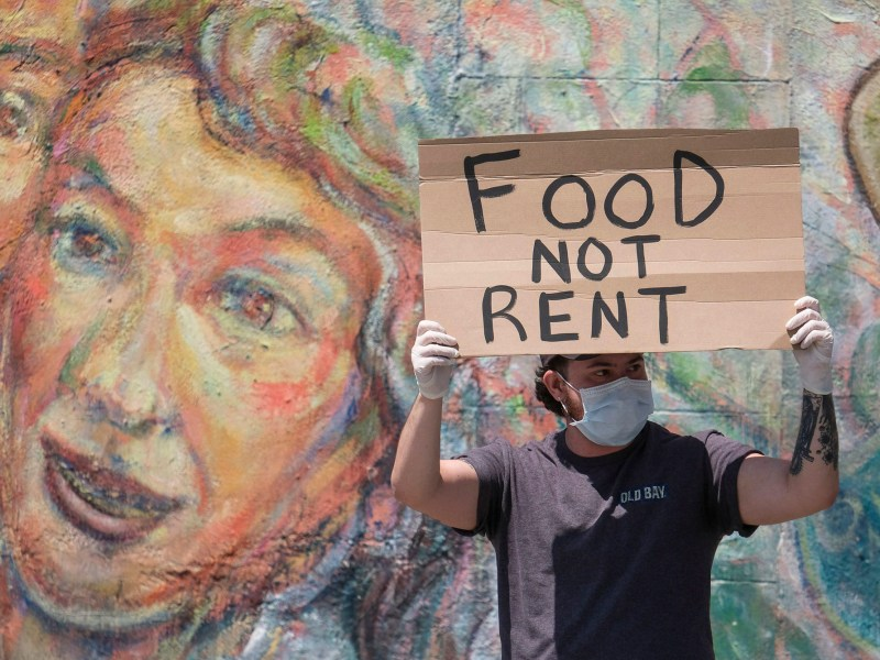 A protester holds up a sign during a rent strike demonstration in Los Angeles on April 21, 2020. Photo by Ringo Chiu, ZUMA Wire via Alamy Live News