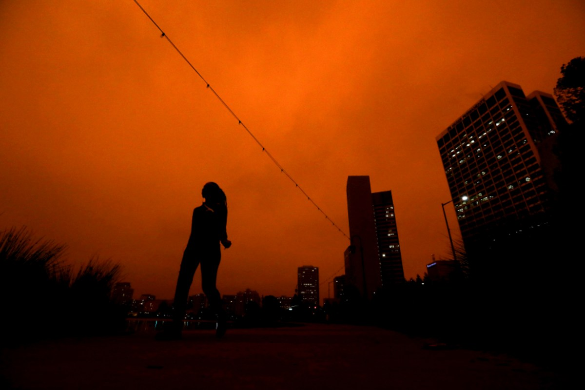 A pedestrian walks around Lake Merritt on Sept. 9, 2020, in Oakland. Smoke from multiple fires in California has filled the Bay Area sky. Photo by Aric Crabb, Bay Area News Group