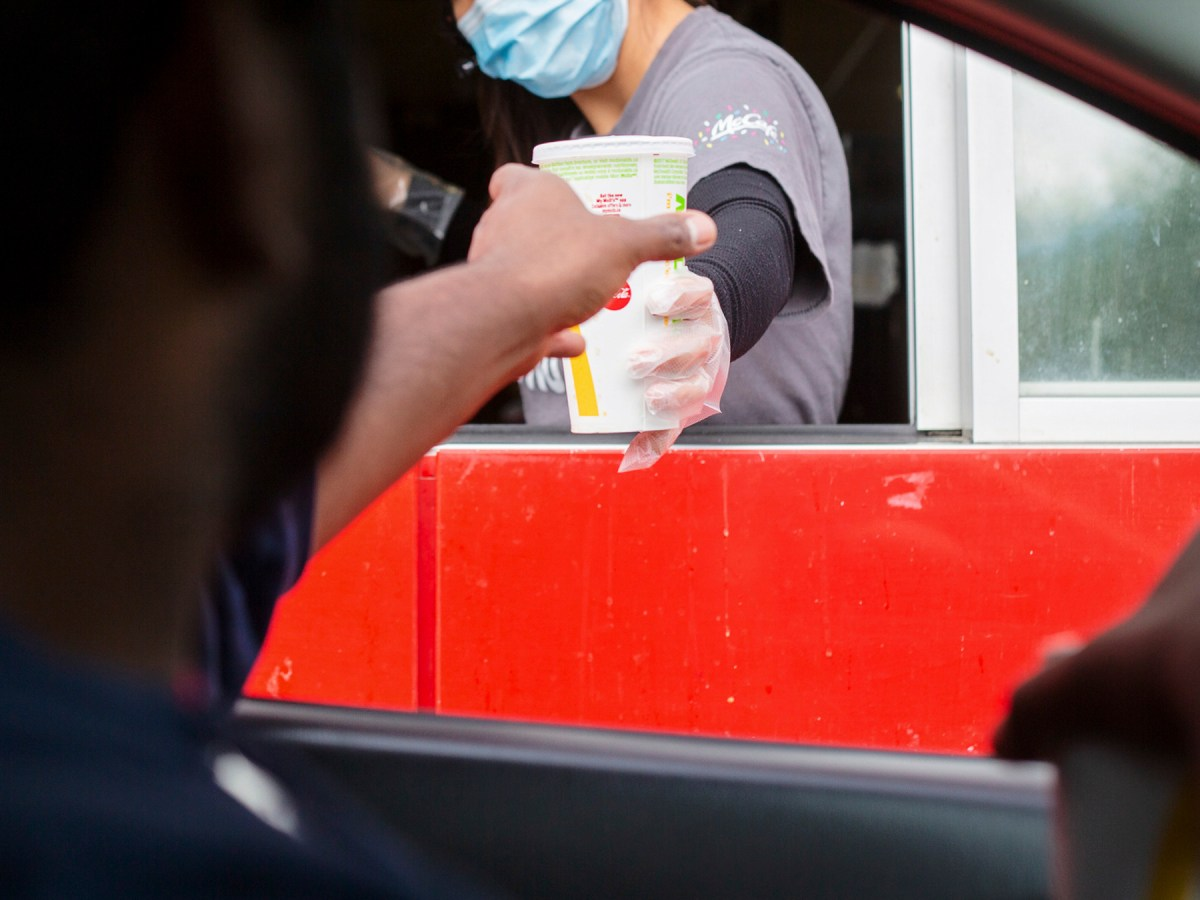 A man reaches for his food at the McDonalds drive-thru window. Image via iStock