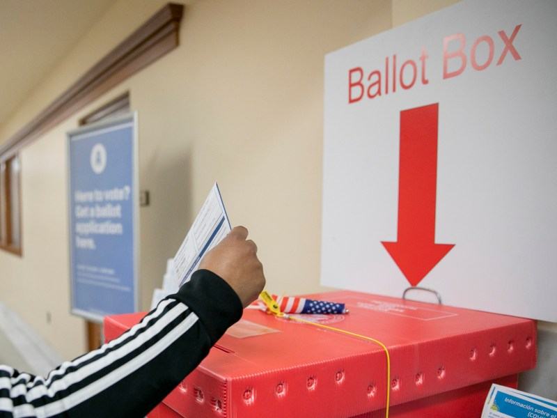 A voter drops her ballot into the box at San Francisco City Hall on Super Tuesday 2020. Photo by Anne Wernikoff for CalMatters