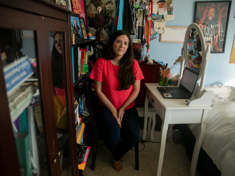 Sarah Rivas, 27, sits for a portrait at her desk where she teaches high school history from her childhood bedroom at her parents' home in Elk Grove, Calif., on Oct. 13, 2020. Rivas, who moved back in with her parents during lockdown and subsequently gave up her apartment in Silicon Valley, worries that she would be unable to afford a new apartment if she were to return to teaching on campus. Photo by Anne Wernikoff for CalMatters