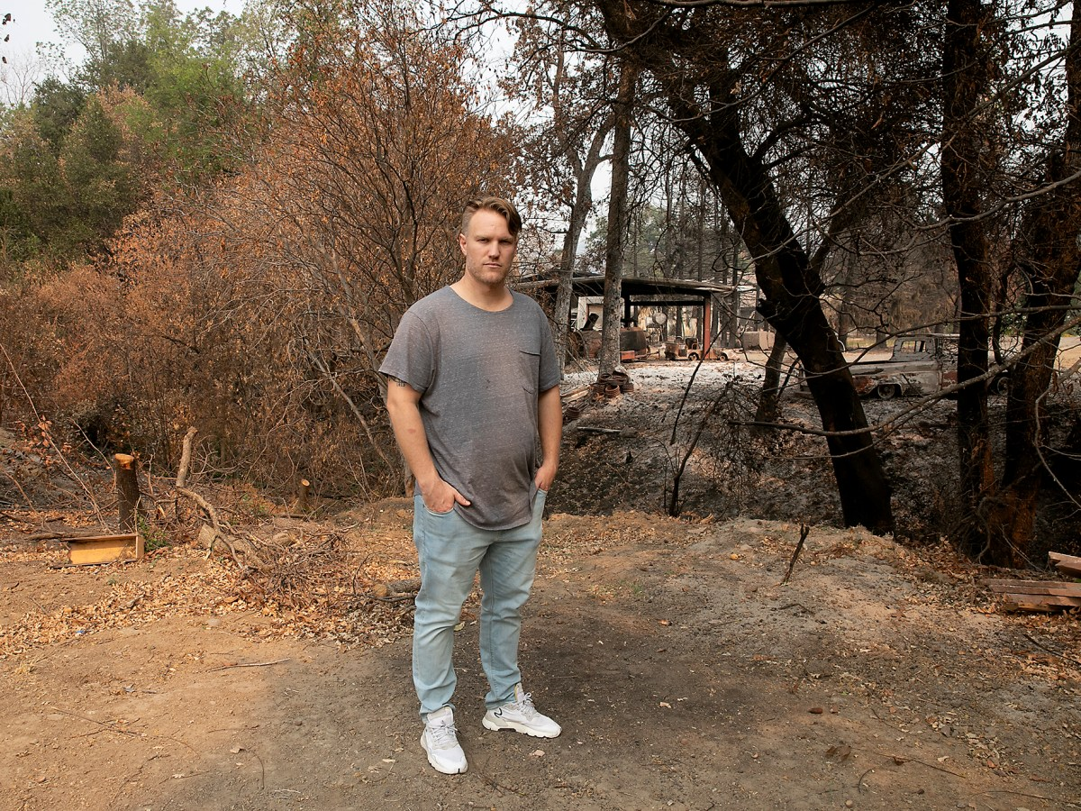 Taylor Craig stands for a portrait on the edge of his family's property outside of Vacaville on Oct. 2, 2020. Charred trees and ground on the adjoining property were caused by the LNU Lightening Complex Fire in August; Craig was able to fight off the flames and protect his home from the fire after not receiving an evacuation warning. Photo by Anne Wernikoff for CalMatters