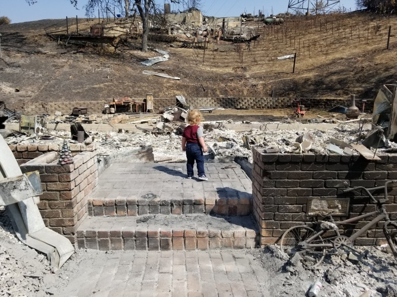 Levi Petrini stands in the ruins of his family's burned Berryessa Highlands home. Photo courtesy of Kody Petrini.
